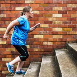 woman doing HIIT exercise on steps outdoors