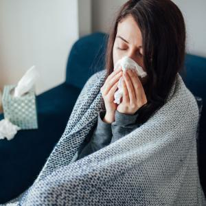 Sick-woman-blowing-her-nose